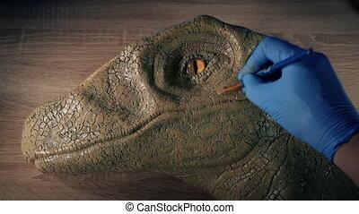 Man paints a model raptor dinosaur head in studio