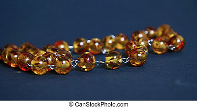 Rare amber necklace isolated on blu