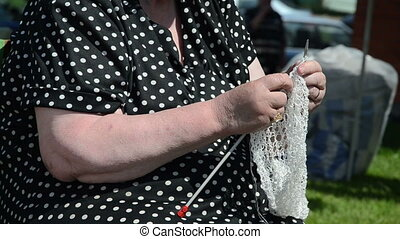 BIRZAI, LITHUANIA - JUNE 08: a woman with a black dress knits knitting needles rare knitted fabrics in white thread on June 08, 2013 in Birzai.
