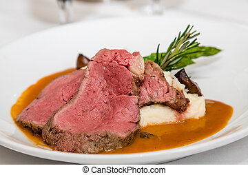 Rare Prime Rib with Potatoes and Rosemary - Serving of rare...