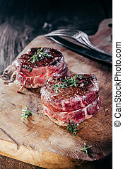 Rare Seasoned Venison Steak Filets on Wooden Board