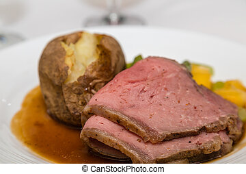 Rare Sliced Beef with Baked Potato - A dinner of sliced...