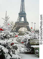 Rare snowy day in Paris. The Eiffel Tower and decorated Christmas tree