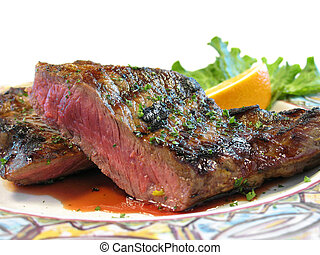 Rare steak on a plate isolated with an orange for garnish