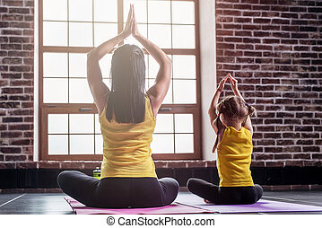 Rare view of two girls practicing yoga sitting in lotus pose meditating