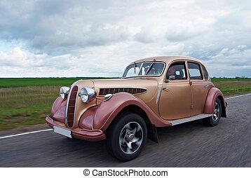 rare vintage car rushing along the road