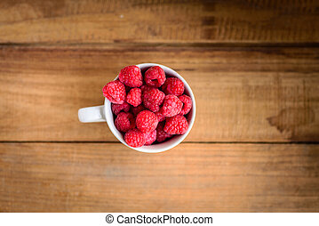 Rasberries in cup on wooden background.