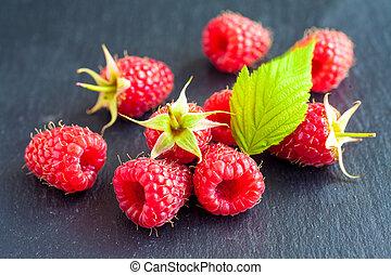 Fresh rasberry on black stone background. Natural food.