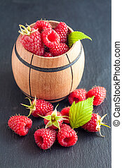 Rasberry in wooden bowl on black stone background. Natural...
