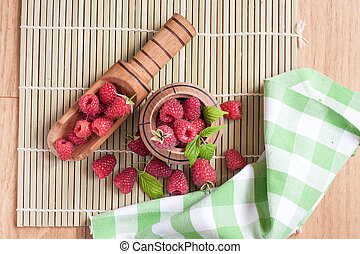 Rasberry in wooden bowl on wooden background. Natural food.