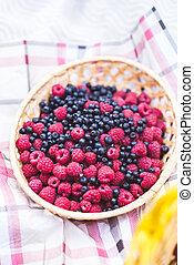 Raspberries and blueberries in a basket - Fresh berries...