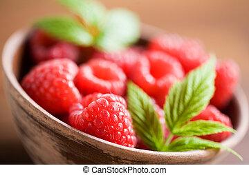 Raspberries - Fresh raspberries in brown bowl, shallow focus