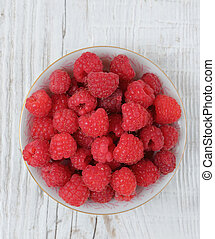 Raspberries in a bowl on a wooden table