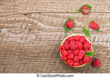 Raspberries in a bowl on the old wooden background with copy space for your text. Top view