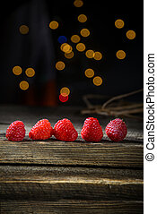 Raspberries in a row on a barn wood board with lights in the background