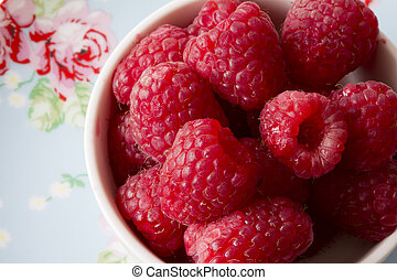 Raspberries in a White Bowl Top View on a floral Backfround