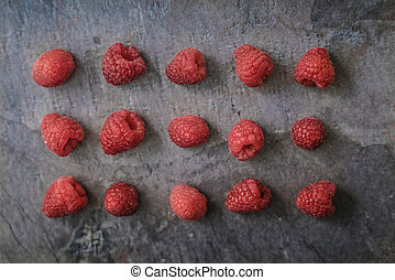 Raspberries on the dark stone background