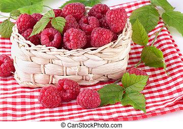 raspberries with leaves in basket