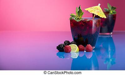 Raspberry and blackberry cocktail with mint garnish. Studio shot