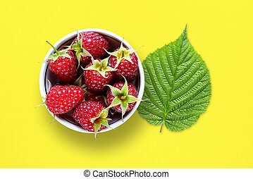 Raspberry and green leaf on yellow table