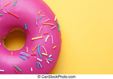 Raspberry donut with icing on a yellow background.