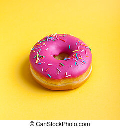 Raspberry donut with icing on a yellow background. Top view. Minimal concept