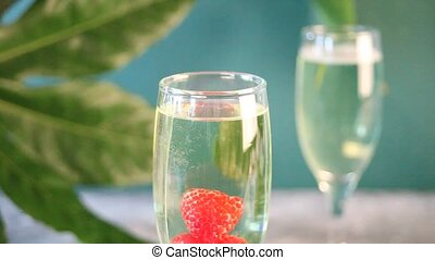 Raspberry falling into a glass of champagne.