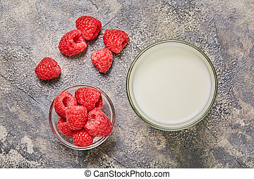 Raspberry, glass milk on gray background. Top view.