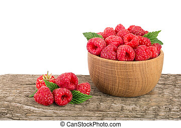 Raspberry in a wooden bowl on table with white background