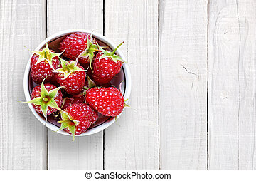Raspberry in bowl on white wooden background