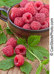 Raspberry in the cup on wooden background