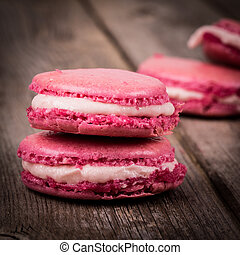 Raspberry macarons over old wood background. Retro cross-processed, vintage effect with intentional vignette