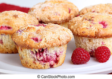 Several whole cranberry muffins and raspberry fruit on a platter