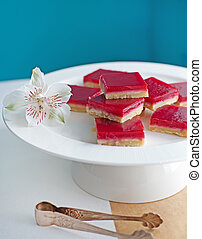 Raspberry shortcrust layered pastry squares on a white plate. Turquoise background