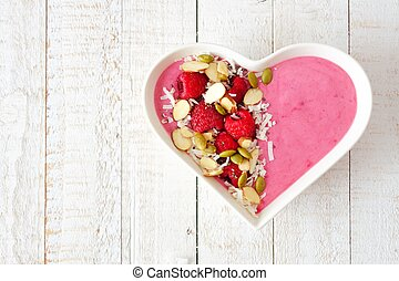 Raspberry smoothie in a heart bowl with superfoods over white wood.