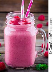 Raspberry smoothie in mason jar on rustic wooden background