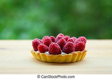 raspberry tarts on a wooden table