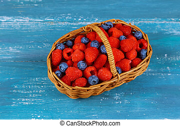 Raspberry with blueberry in basket on an old blue board