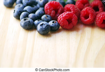 Raspberry with blueberry on wooden table