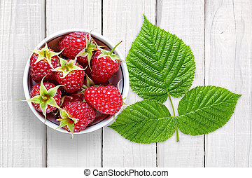 Raspberry with leaves on white wooden background