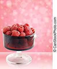 Rasperries in glass red bowl