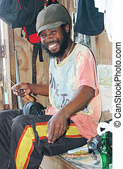 rasta craftsman smiling with threading tool