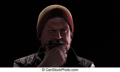 Rastafarian hat hipster old man wink on camera in a semi lit light room isolated on a black background. Prores 422