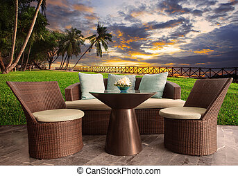 rattan chairs in outdoor terrace living room against ...