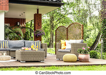 Rattan garden furniture with grey pillows, table with fruit on a terrace in a spa