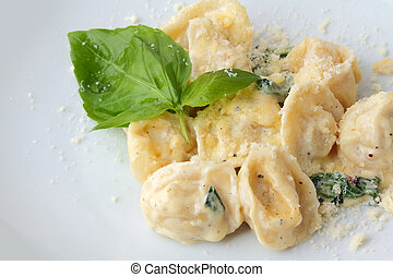 close up ravioli stuffed with chicken in a creamy sauce with spinach