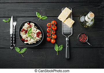 Ravioli pasta with mushroom cream sauce and cheese - Italian food style with basil parmesan and tomatoe in black bowl, on black wooden table background , top view flat lay , with copyspace and space for text