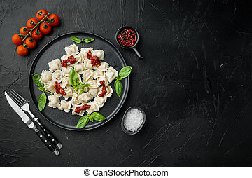 Ravioli pasta with mushroom cream sauce and cheese - Italian food style with basil parmesan and tomatoe on black plate, on black background , top view flat lay , with copyspace and space for text