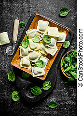 Ravioli raw on a plate with spinach.