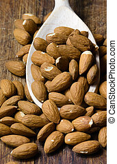 Raw almond on wooden spoon in brown background